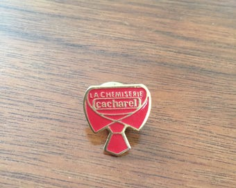 Vintage pin badge perfume advertising Cacharel La Chemiserie shaped pin