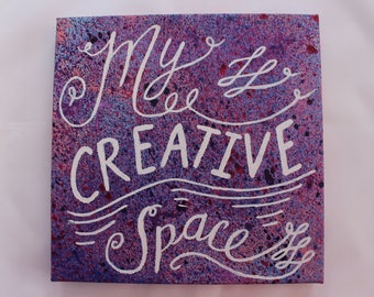My Creative Space Canvas for your creative space.  White hand lettering on a Purple and Pink splattered background. 8 x 8 inches