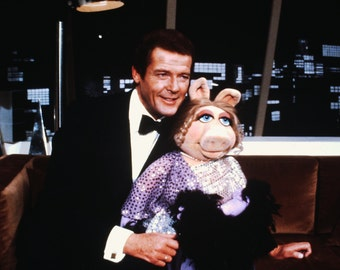 Roger Moore w/Miss Piggy on a Muppet Show slide
