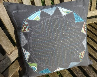 A variety of blues patchwork and embroidery on a cotton/linen cushion.