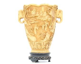 Large decorated ivorine vase on foot of composite.