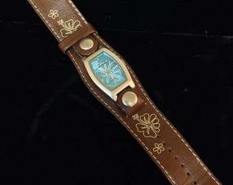 Anchor Blue ladies quartz watch with wide leather strap. Matching blue hibiscus flower motif on strap & dial.