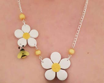 White flowers and a bee necklace