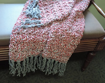 gray, red, white crocheted throw with fringe