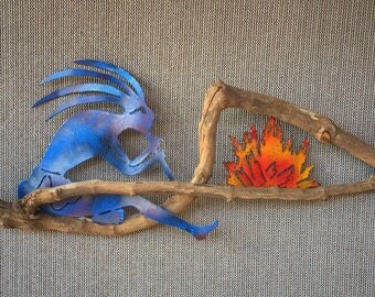 Kokopelli Playing Flute By Fire On Wood