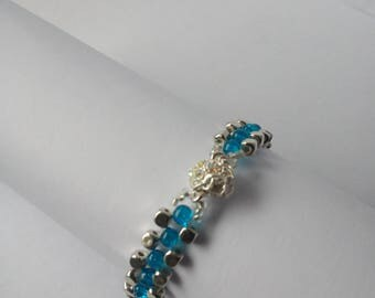 A blue and silver cubed beaded bracelet with clear crystals on a silver plated magnetic clasp with a safety chain