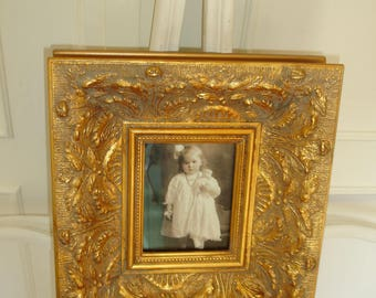 Little girl with rosey cheeks clutches her dolly framed print.  Lovely