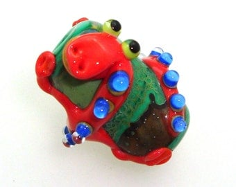 Handmade Lampwork Glass Beads - Coral lizard with blue bumpy dot spine on grass green with silver glass shards.