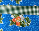 Reversible oilcloth placemats with fruit clusters on blue and green gingham