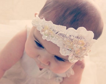 Dress-up Headbands of Lace, Pearl Beads & Sequins for Baby securely placed on a comfortable stretchy headband.