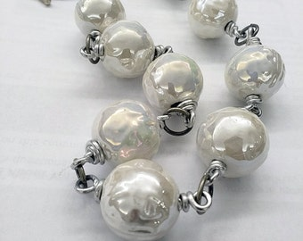 Metal necklace with large shiny ceramic beads.