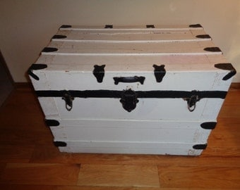 Antique Storage Trunk  in Good Vintage Condition with a black and white painted exterior finish and a cloth covered upholstered interior