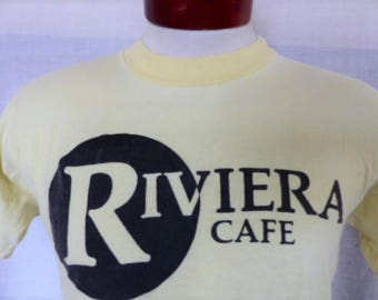 vintage 70's 80's Riviera Cafe pale yellow graphic t-shirt black circle logo print advertising promo tee crew neck tee Sportswear medium
