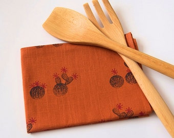 Hand block printed tea towel in 100% linen, orange with a cactus design in grey/pink.