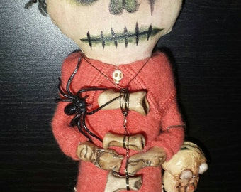 Stuffed fabric Zombie doll, holding skull made out of paper clay, all handmade, polymer clay bone necklace and hands. Stuffed with Polyfil.