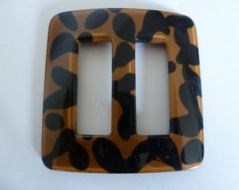 A lustrous, slightly rounded and curved, tan and black spotted buckle; the material is acrylic and the mood is tres chic! Ideas, anyone?
