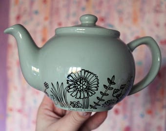 Hand drawn small porcelain light green teapot with flowers design florals botanicals