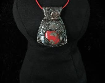 Polymer clay cabochon framed with unique designs on red leather cord