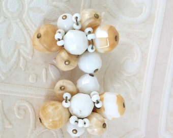 Signed HATTIE CARNEGIE clip earrings hand wired with beige and white glass beads of different sizes, vintage gold toned cluster caramel