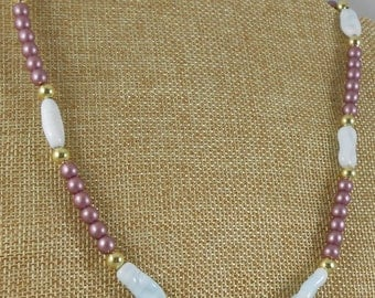 Necklace featuring mauve Czech glass beads with vintage elongated pale blue beads and gold finish spacer beads