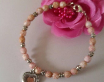 Sweet Pink and silver  beaded bracelet with silver and pink and silver  heart charm Adult size. Made with memory wire.