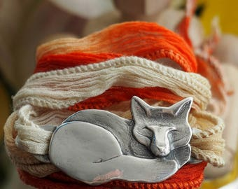A gorgeous fox hand made in fine silver on a hand dyed orange silk wrap bracelet...