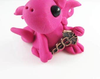 Polymer clay hot pink baby dragon with a medical caduceus