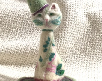 Sitting pretty/felted cat on rug