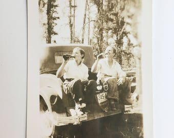 vintage photo of women sitting on the back of a car drinking beer