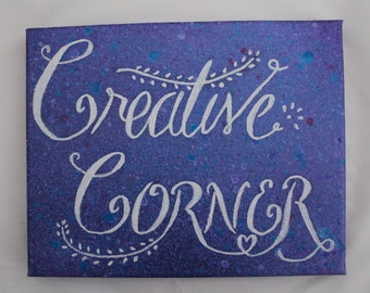 """Creative Corner Canvas for your creative space.  White hand lettering on a Purple with hints of blue and pink splattered background 10"""" x 8"""""""