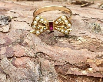 Late 19th century 9ct gold bow ring with rubies and seed pearls