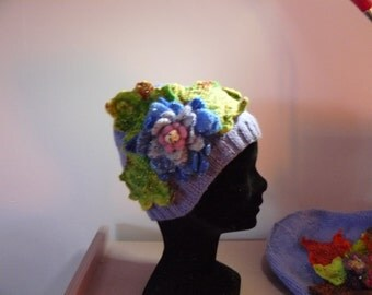 Purple woman Hat adorned with leaves and a large blue water lily