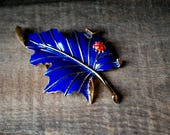 Classy vintage 70s, gold tone metal leave brooch with a navy blue enamel and red lady bug.Made by Trifari.