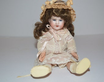 Vintage pretty doll - dressed in lovely outfit - porcelain head and brown wig