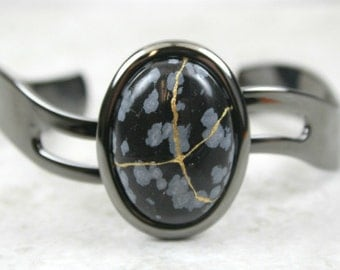 Kintsugi (kintsukuroi) cuff bracelet with snowflake obsidian stone cabochon with gold repair in a gunmetal black plated setting - OOAK