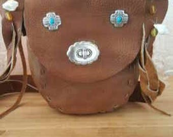 A leather over the shoulder handbag, Flap closure has a swivel button with inside flaps to secure items in the purse.