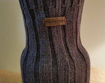 Ribbed pattern with columbia leather emblem. Grey/brown color. Heavy glass vase inside.