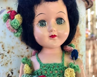 50's doll/ crocheted hula outfit /hard plastic doll / painted on eyelashes / thin eyebrows / blinking green eyes /green doll outfit with Lei