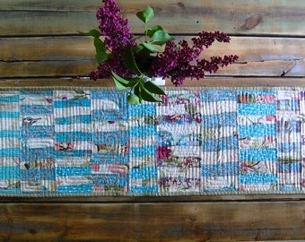 Pieced and quilted table runner in turquoise and plum