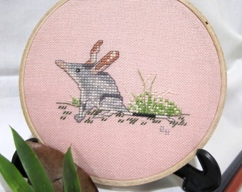 Hand cross stitched Australian hoopart - Bilby. Home/wall decor gift item. Dusty pink coloured evenweave fabric in 13cm wooden hoop.