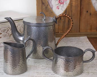 Vintage hammered English pewter tea set. Pot, sugar bowl and creamer, with rattan handle.