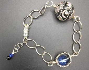 Bright Silver Chain Bracelet with blue and black accent.