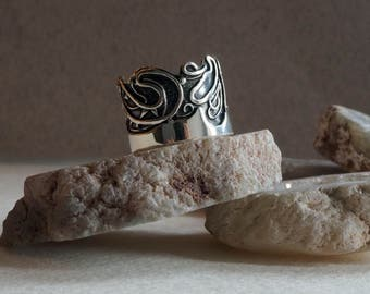 Silver wide ring with torn edge and abstract pattern. Asymmetric band.