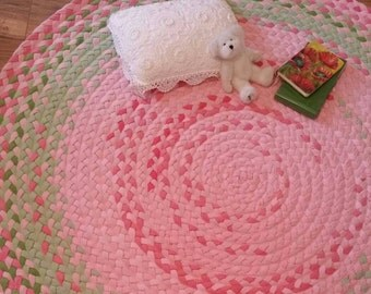 "56"" Blush pink braided nursery rug, with kiwi green accents"