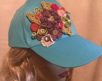 Teal Baseball Cap decorated with A Collage of Pastel Flowers Buttons and Green Wire Accents