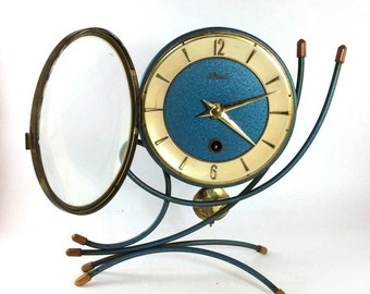 Atomic age Hermle wind up mantel clock in a futuristic metallic blue bent wire metal frame. Brass hands and numerals.