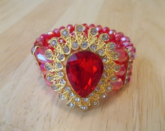 Reduced 3 Row Red Crystal Stretch Cuff Bracelet with a Gold Tone Pendant with a Red Crystal Center surrounded by Clear Rhinestones