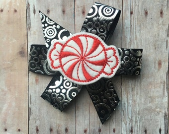 Peppermint candy pinwheel bow on partially lined alligator clip with no slip clip - black with silver foil circles - approx. 4 inches across