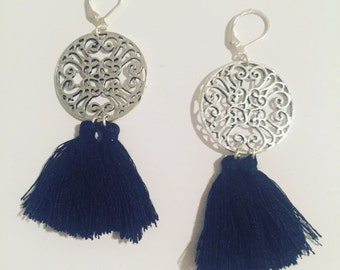 Ornate dangling earrings of two black tassels