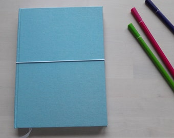 Sketchbook with bright white paper and soft blue linnen cover. Ideal for sketches, notes (blank notebook) and doodles (doodle journal)